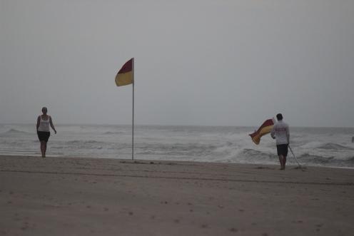 Man carries a flag towards a woman